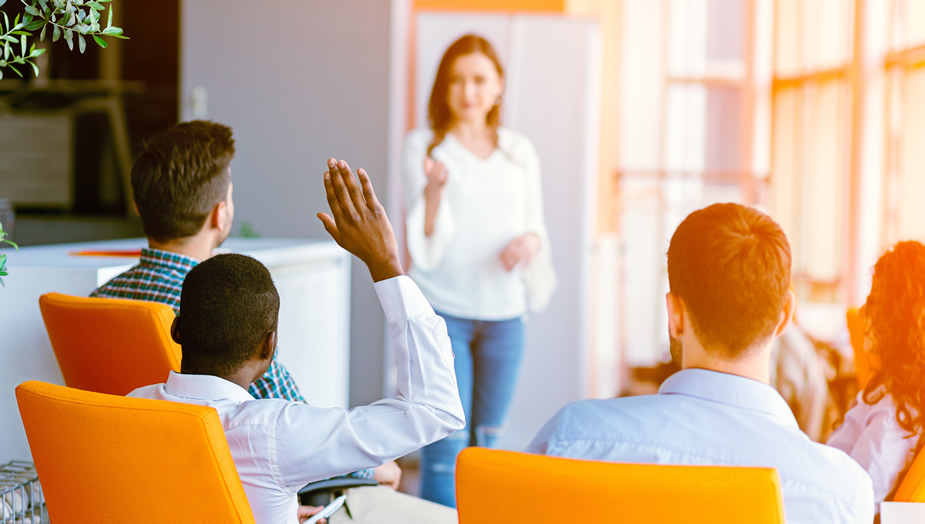 person raising hand in group