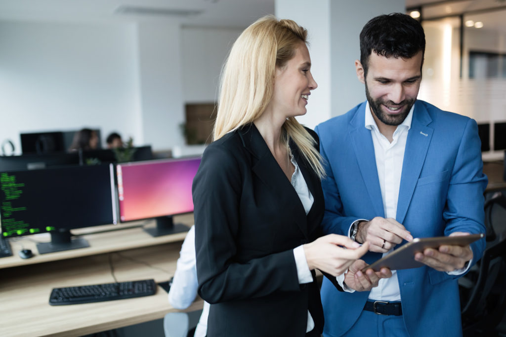 two people smiling looking at tablet computer